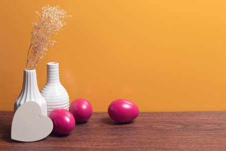 table with close up vase and food vintage colorful pink easter eggs with wood vine and flower on yellow background Stock Photo