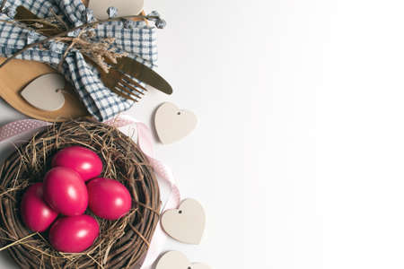 easter eggs pink color on background with spoon and fork and dried grass with wood vine and flower