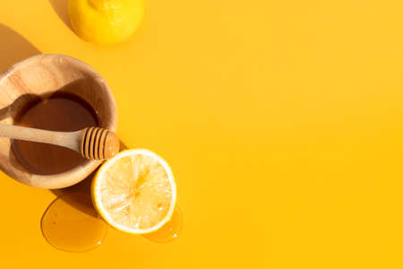 sweet organic natural honey lemon fruit with wood dish cup in kitchen on yellow background, fresh food drink, summer season Фото со стока