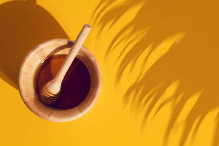 honey with wood dish cup in kitchen on yellow background organic natural, fresh food drink, summer season Фото со стока