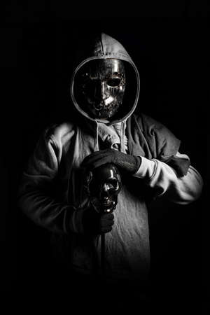 man in halloween costume of ghost evil with black metal mask and wear hooded in darkness concept