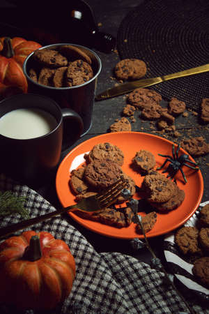 sweet biscuit cookies dessert and milk with halloween holiday dinner prop decoration with wood table background
