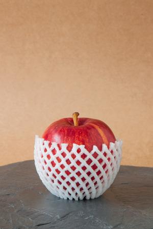 piso piedra: manzanas rojas con embalaje de protecci�n en suelo de piedra Foto de archivo