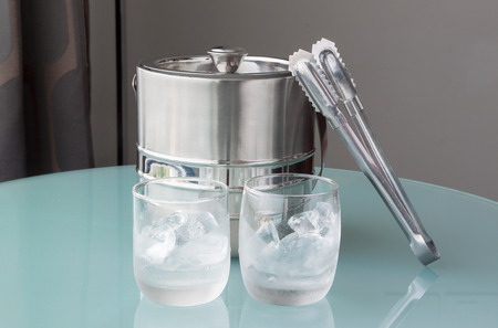 ice water: Glass of cold water and ice with stainless bucket