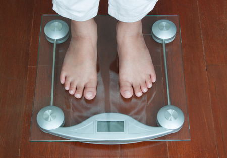 cipher: Woman Standing on Digital Weighing Apparatus Stock Photo
