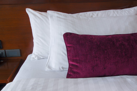 violet residential: White and violet  pillows on a bed