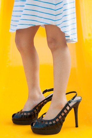 big shoes: Little girl in big shoes on yellow backgrounds