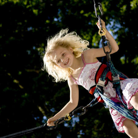 young girl bunji jumping securely on trampoline photo