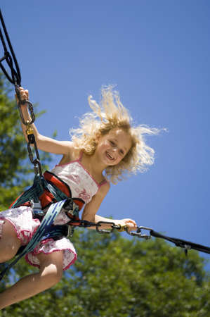 young girl bunji jumping securely on trampoline