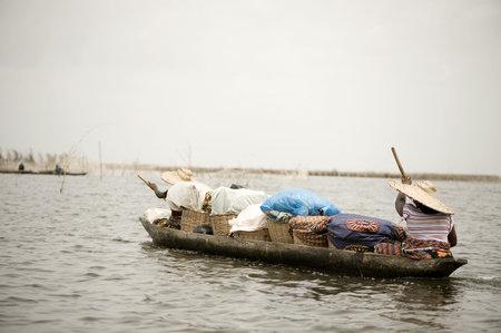 Women boating on the lagoon of the stilt village Ganvie in Benin. photo