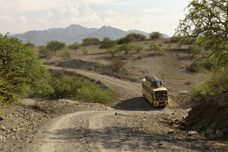 Bus traveling on dirt road, Tanzania, Africa photo