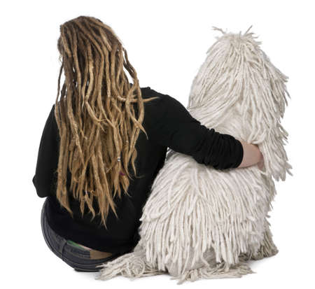 Rear view of a White Corded standard Poodle and a girl with dreadlocks sitting in front of white background photo