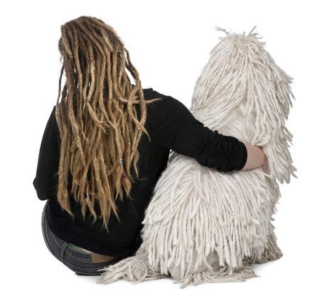 dreadlocks: Vista trasera de un blanco cuerdas Poodle est�ndar y una ni�a con dreadlocks sentado delante de fondo blanco  Foto de archivo