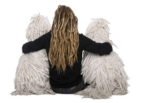 Rear view of two White Corded standard Poodles and a girl with dreadlocks sitting in front of white background photo