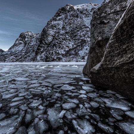 Winter landscape on a lake during Lofoten islands winter. Snow and ice melting 版權商用圖片 - 160879598