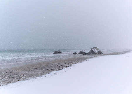 Beach along the Norwegian coast, covered with snow during a snowstorm Stockfoto