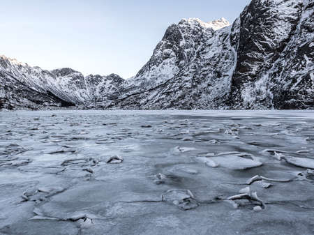 Winter landscape on a lake during Lofoten islands winter. Snow and ice melting