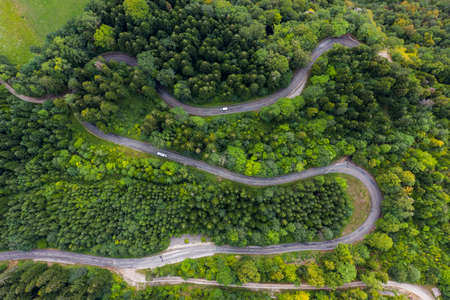 Aerial view of a winding countryside road passing through the green forest and mountain. White camper van are passing through. Stockfoto