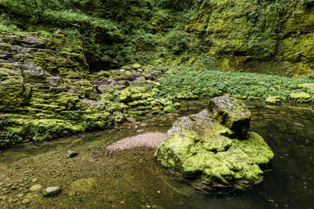 Still water and stones covered by moss at Nans-sous-sainte-Anne, Pit cave