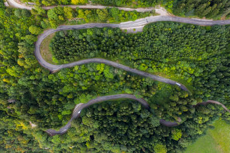 Aerial view of a winding countryside road passing through the green forest and mountain. White camper vans are passing through. Stockfoto