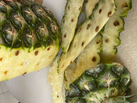 Large knife peeling whole pineapple on the desk in a kitchen 版權商用圖片