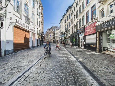 Brussels, Belgium, April 25, 2020 - Rue marché aux herbes, a family cyclists on a deserted street in the old quarter of Brussels during the crisisConfinement covid-19