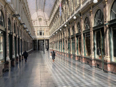 Brussels, Belgium, April 25, 2020 - two people inside the luxury glazed shopping arcade Les Galeries Royales Saint-Hubert during the Confinement covid-19 新聞圖片