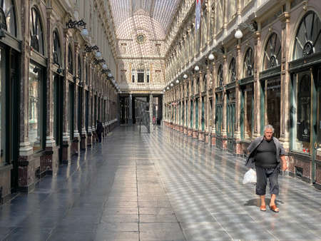Brussels, Belgium, April 25, 2020 - one people walking alone inside the luxury glazed shopping arcade Les Galeries Royales Saint-Hubert during the Confinement covid-19