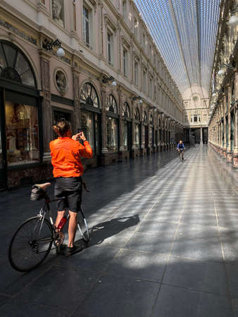 Brussels, Belgium, April 25, 2020 - two cyclist inside the empty luxury glazed shopping arcade Les Galeries Royales Saint-Hubert during the Confinement covid-19