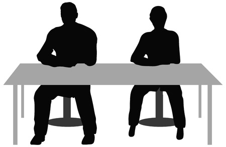 sit down:  Two business people sitting a desk.