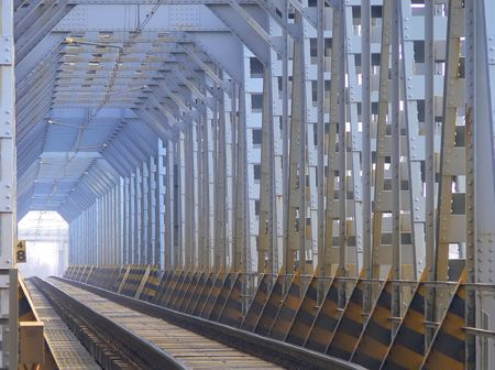 Picture of a railway bridge whit long parallel lines and a particular light at the end of the tunnel photo