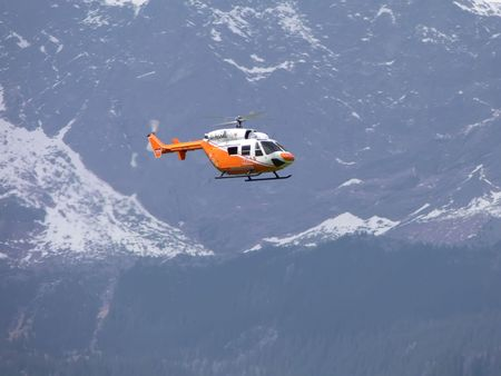 White and orange helicopter ambulance flying through the mountains Stock Photo - 3694372
