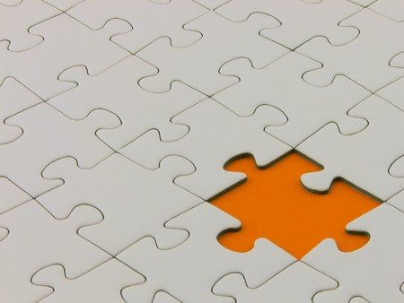 incomplete: Close up of an incomplete white puzzle with a missing orange piece Stock Photo