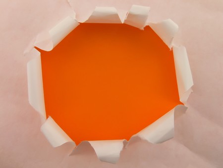 Picture of an empty hole in a white sheet with orange background photo