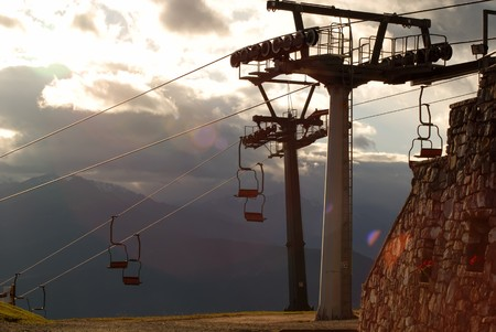 chair lift: Close up picture of a chair lift with mountain range, sky and clouds Stock Photo