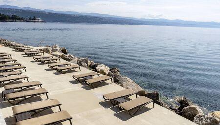 Beach with umbrellas and sun beds, ready for the summer. Croatia Opatija. Zdjęcie Seryjne