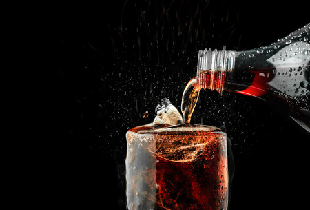 Pour soft drink in glass with ice splash on dark background. Standard-Bild - 119408745