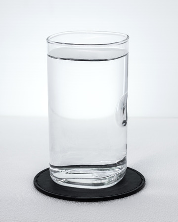 Black beverage coasters with water glass on white background. Pure water in transparent glass.