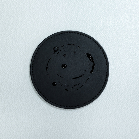 Water stain on black beverage coasters. Blank leather coasters for your design. Banco de Imagens