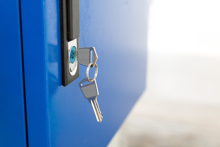 Blue locker and key chain in school gym. Modern metal cabinets and copyspace for your design.