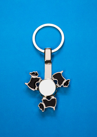 Steel key ring on blue paper background. Blank key chain or fashion accessory for your design. Can put text, image, and logo. Banco de Imagens