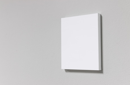 White picture frame on cement wall. Modern gallery in simple style.