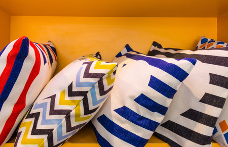 Colorful pillow and design pattern on yellow shelf. Modern cushions and interior furniture. Stok Fotoğraf