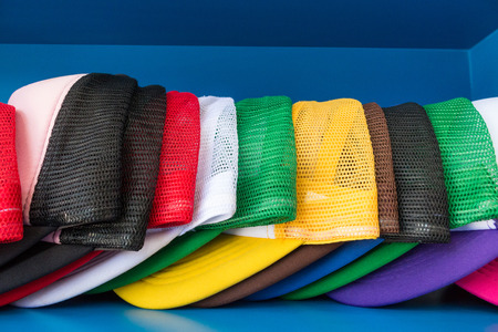 Colorful cap on blue shelf background. Fashion baseball or hiphop hat.