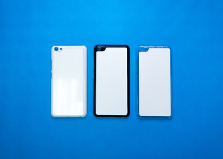 Back view of smartphone cases on vivid blue paper background. Three phone cover or protector for your design. ( Black , white , transparent ) 写真素材