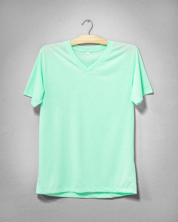 Green shirt hanging on cement wall. Empty clothing for design. Front view. Stock fotó