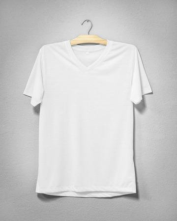 Biała koszula wisząca na cementowej ścianie. Puste ubrania do projektowania. Przedni widok.