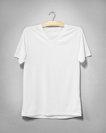 White shirt hanging on cement wall. Empty clothing for design. Front view.