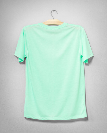 Green shirt hanging on cement wall. Empty clothing for design. Back view.