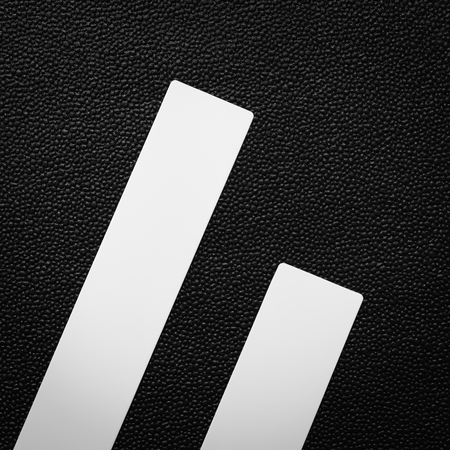 White plastic ruler on dark background. Empty object for design. Фото со стока